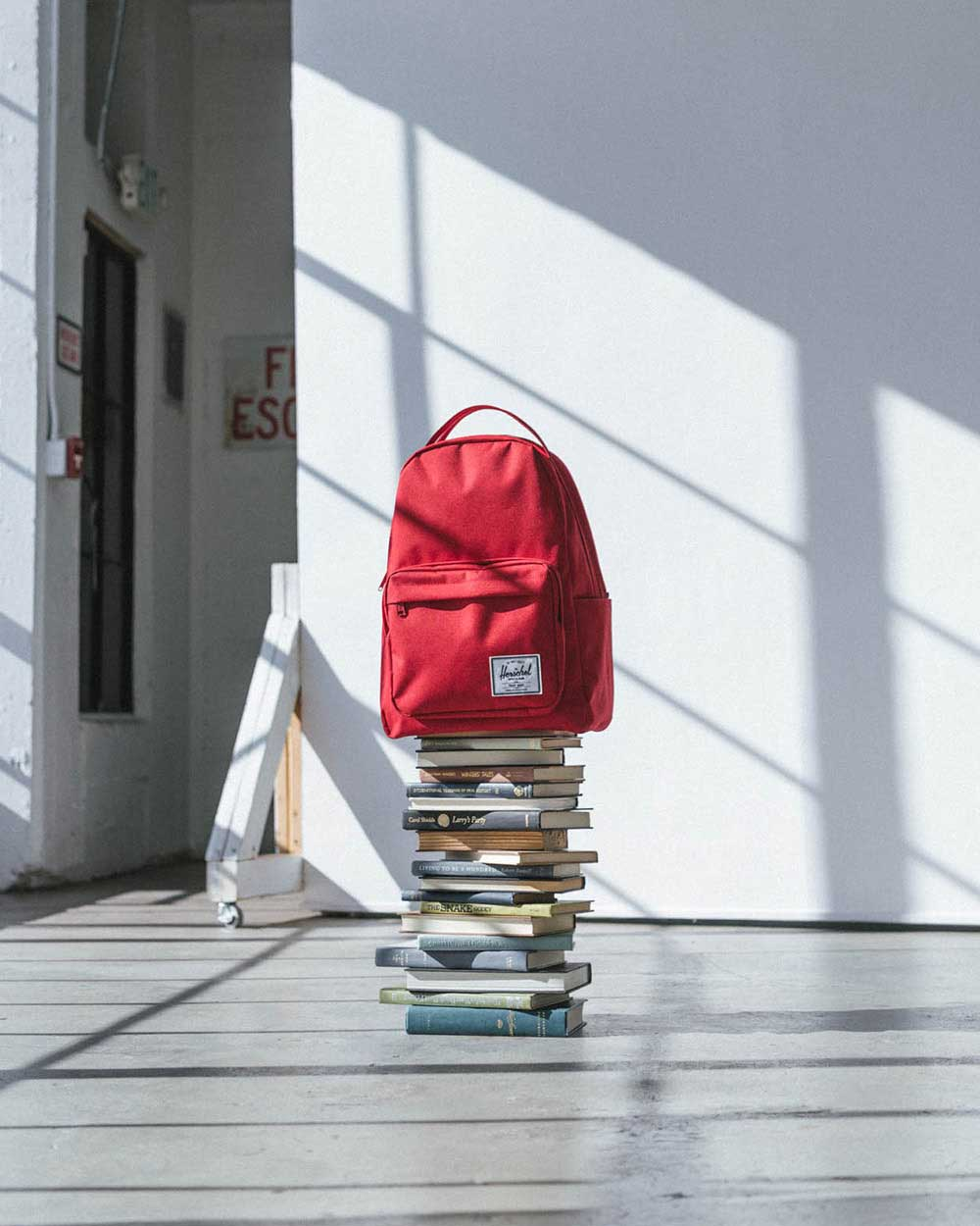 A red Miller Backpack on a stack of books in a studio