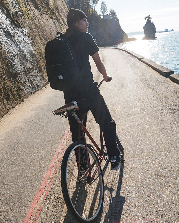 A man riding a bike on a seawall wearing the Settlement Backpack in Black