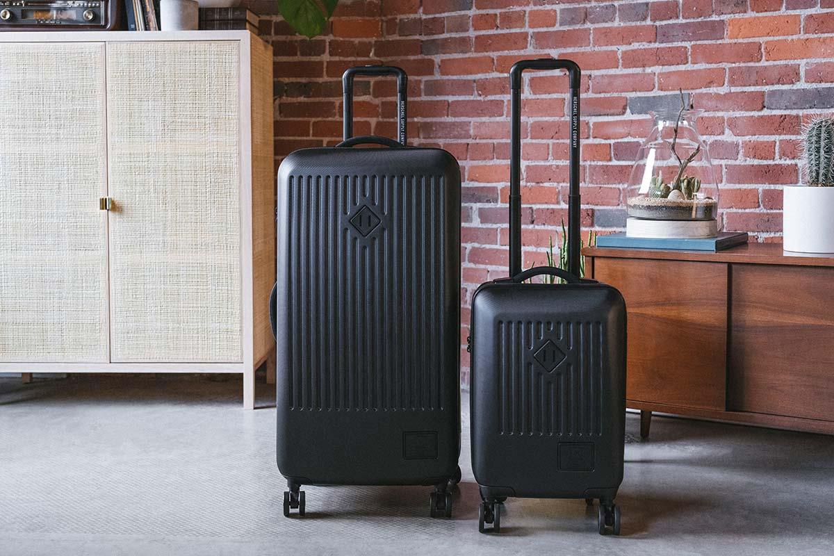 Ein schwarzer Trade Luggage Large und Trade Luggage Carry-On nebeneinander in einer Wohnung mit Sichtbackstein