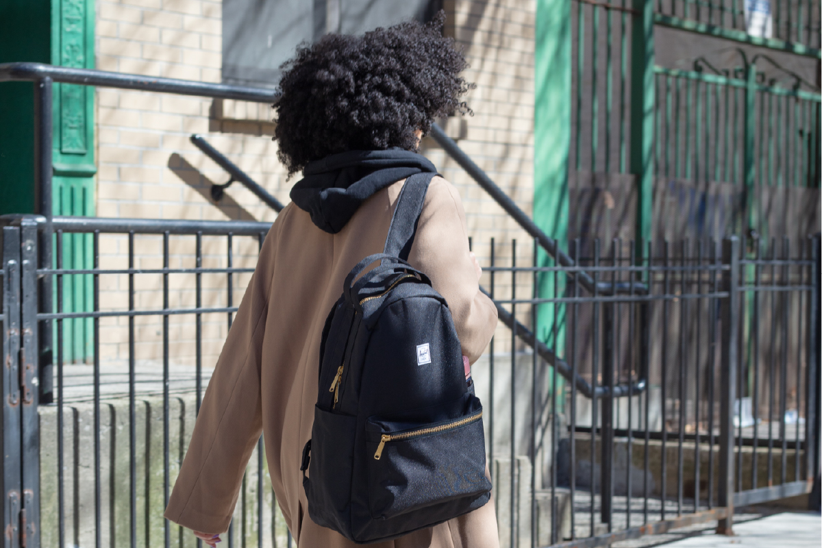 A photo of Erica Lall, a ballerina from New York walking down the street in a black Nova Backpack Mid-Volume