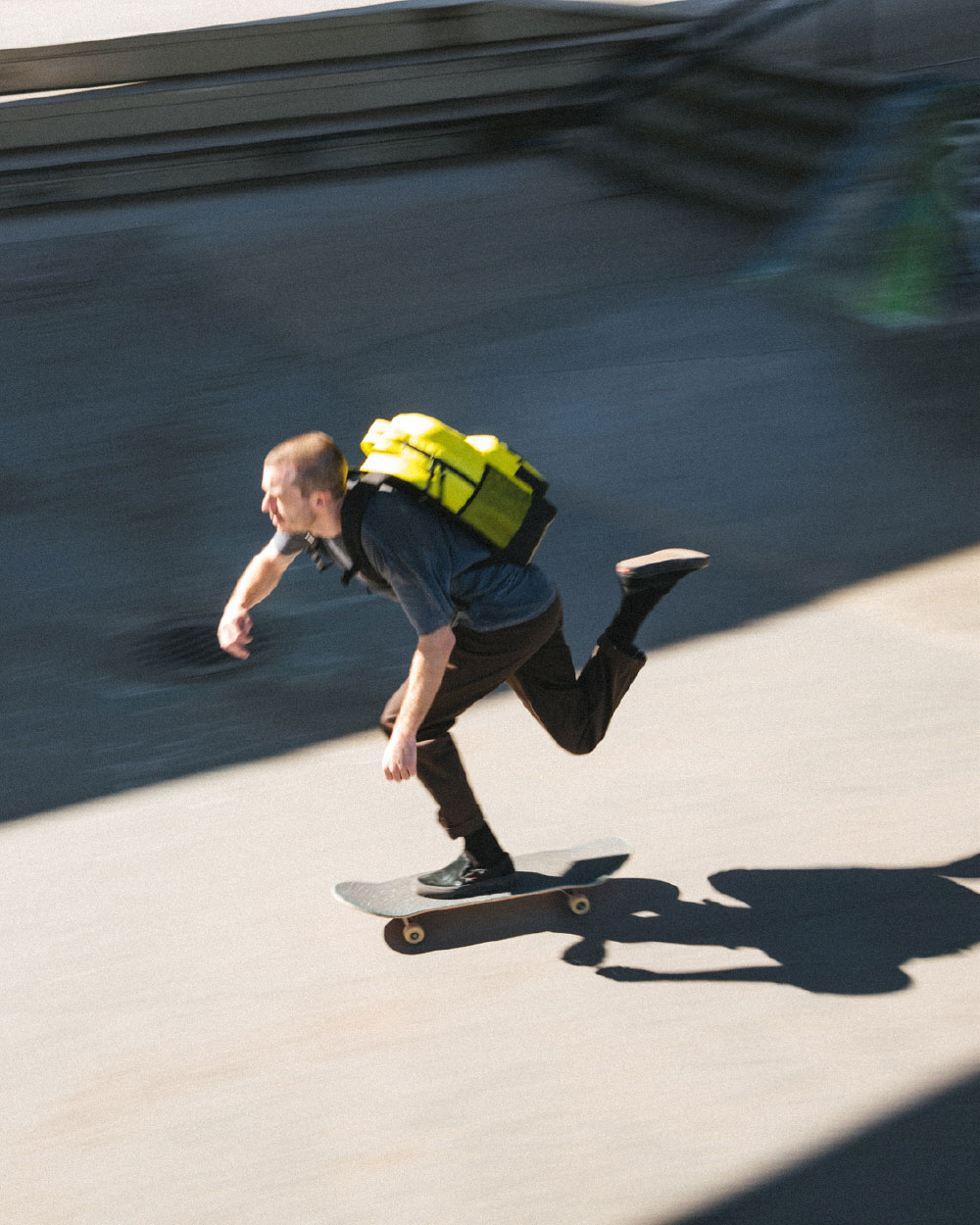 man skateboarding with yellow insulated miller backpack on