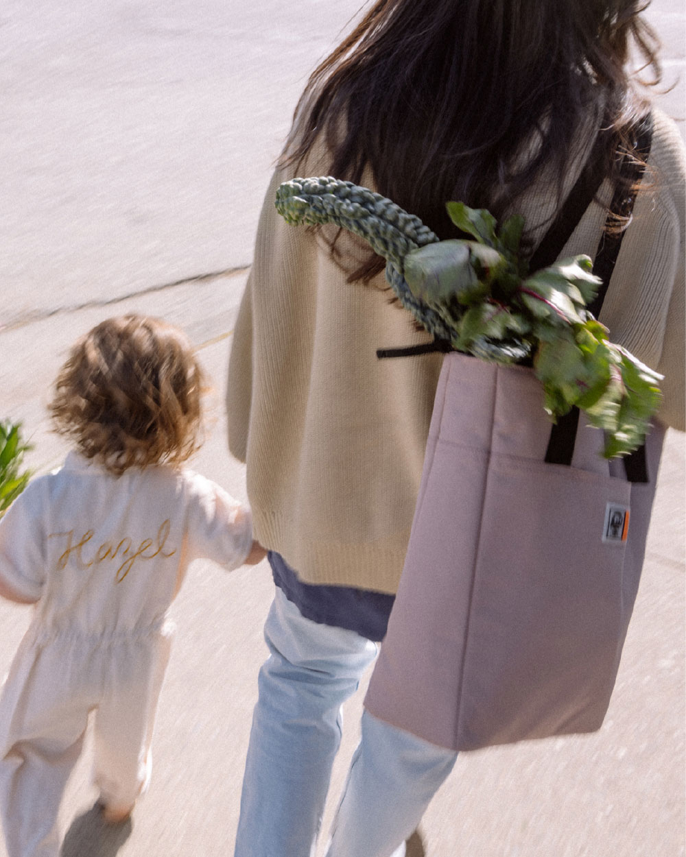 woman with a insulated tote full of groceries walks with her infant daughter.