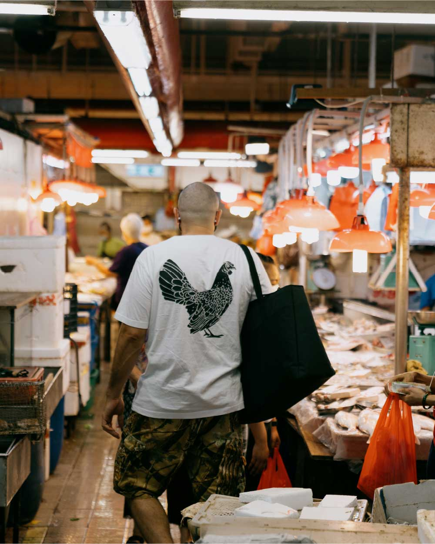 Chef Matt holds a black insulated alexander zip tote while walking through a open air market