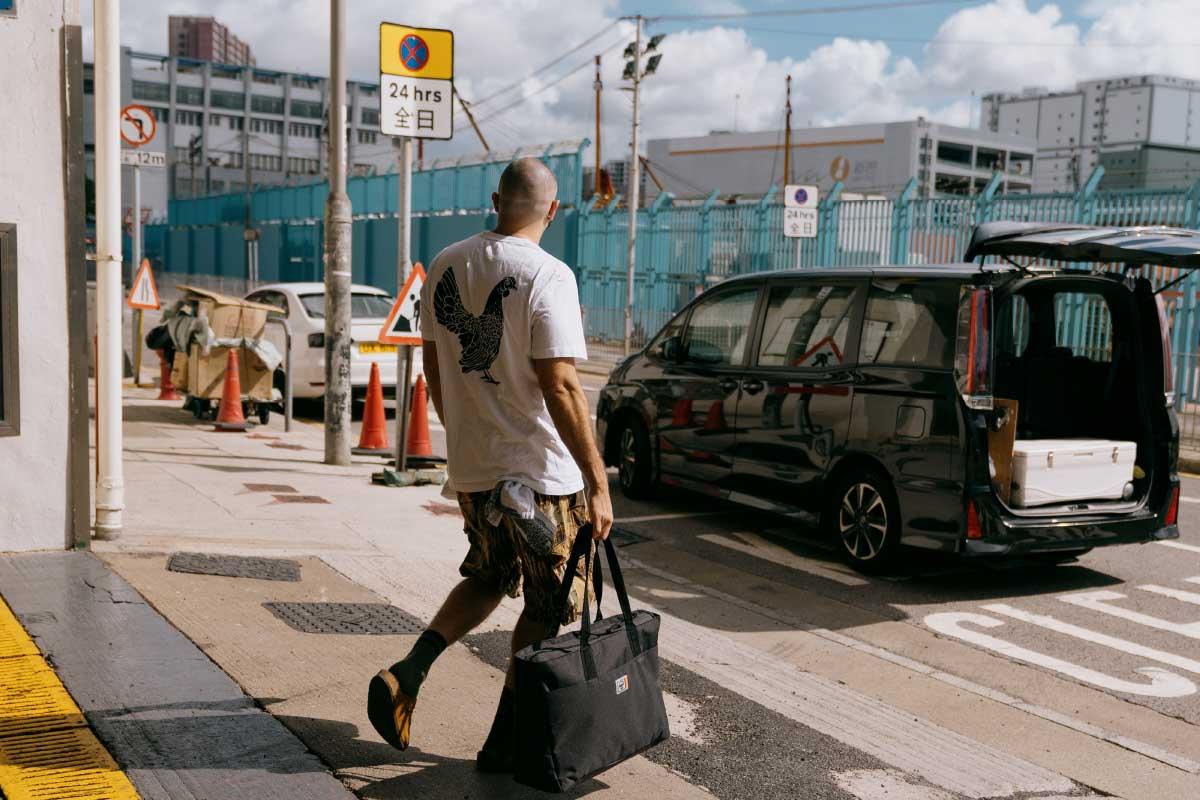 Ein Foto von Erica Lall, einer Ballerina aus New York, die mit einem schwarzen Nova Backpack Mid-Volume die Straße entlang läuft