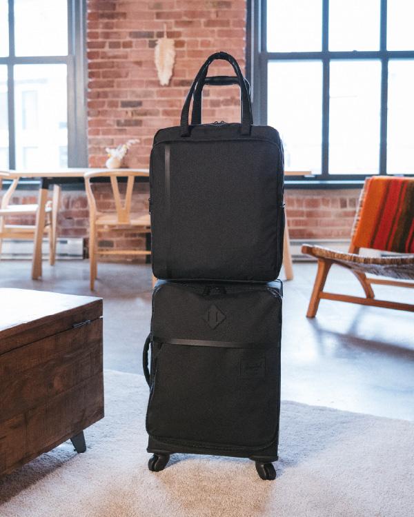 Ein Highland Luggage Carry-On in Schwarz mit einer Tragetasche für Reisen darauf.